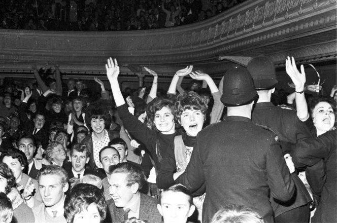 Admin_thumb_fans_at_the_beatles_concert__wellington_town_hall__june_1964._shows_some_standing_and_screaming__being_held_back_by_policemen._other_people_are_seated_nearby._photograph_taken_by_morrie_hill_of_wellington