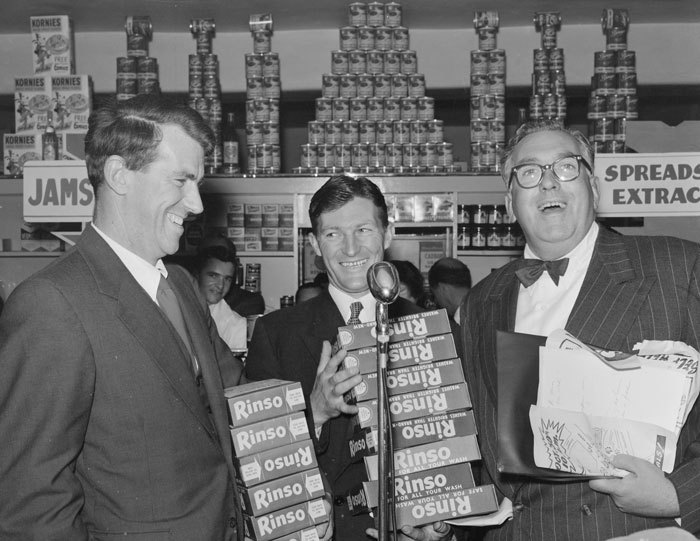 Admin_thumb_sir_edmund_hillary__selwyn_toogood__and_an_unidentified_man__with_give_away_rinso_products_at_the_opening_week_of_the_self_help_store__lambton_quay__wellington__1956